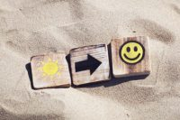 scrabble tiles on sand depicting sun, arrow, and smiley face - next right thing