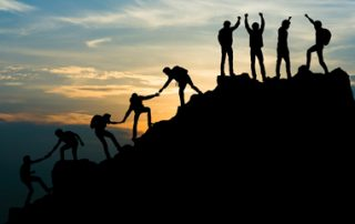 silhouette of backpackers climbing ridge - helping each other up - benefits sober living