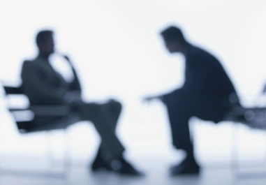blurry black and white image of two businessmen talking - job