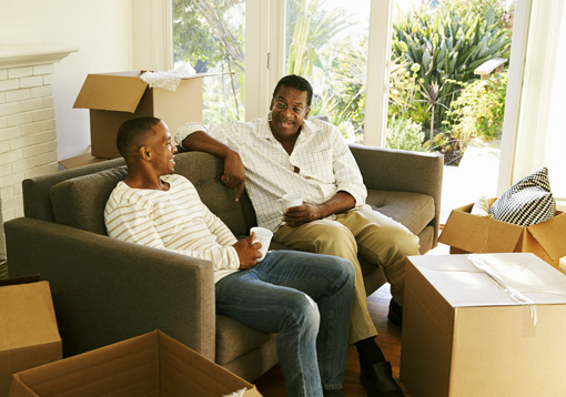 Black young adult man and his father having coffee on moving day - families - substance abuse counseling